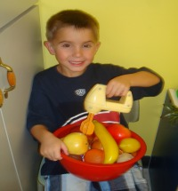 Photo of kindergarten boy pretending to mix a bowl of fruit