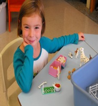 Photo of girl playing with Pet Shop toys